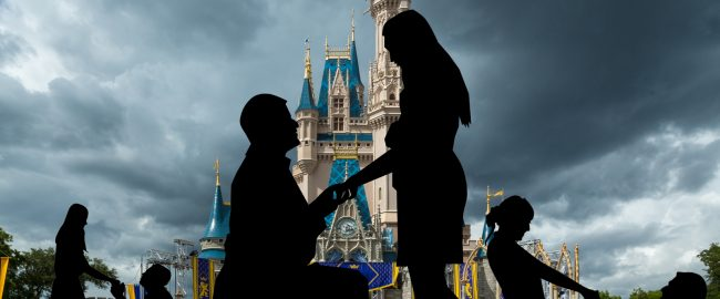 Multiple couples proposing marriage in front of Cinderella Castle