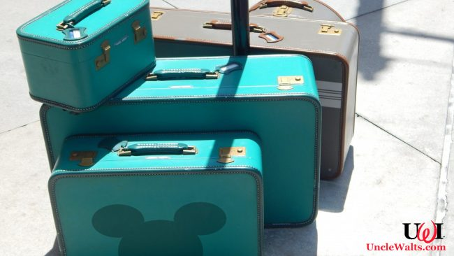 Some suitcases, one of which has a Mickey silhouette on it.