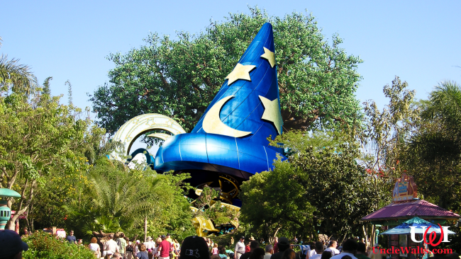 The Sorceror Mickey Hat in its new Animal Kingdom home. Photo credit Mfwills [CC BY-SA 3.0] via Wikimedia Commons and Katie Harbath [CC BY-NC-SA 2.0] via Flikr.