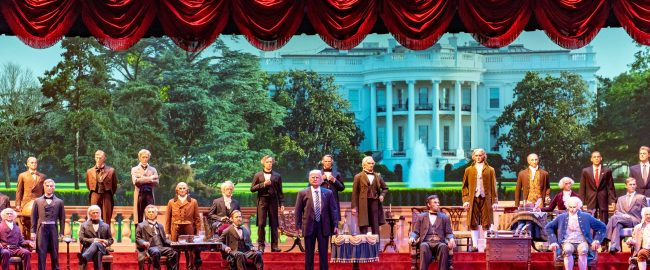 Hillary Clinton (center, in a man's business suit) leads the Hall of Presidents. Photo by Steve Wise [CC BY-SA 2.0] via Flickr.